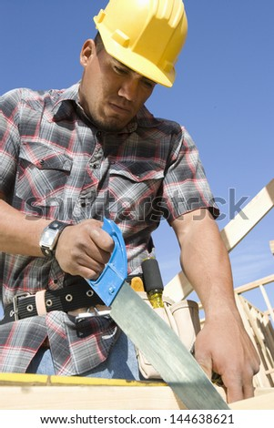 Construction worker sawing on construction site - stock photo