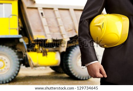 construction worker showing thumb up smiling in beside truck - stock photo