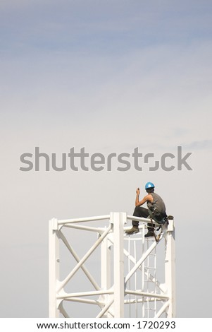 Construction worker sits on top of crane tower - stock photo