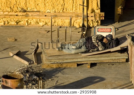 Construction worker sleeps by danger sign on job site - stock photo