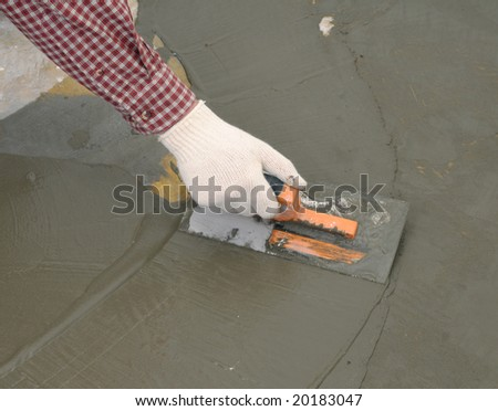 Construction worker spreading wet concrete - stock photo