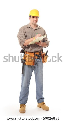 Construction worker standing full length and writing on clipboard - stock photo