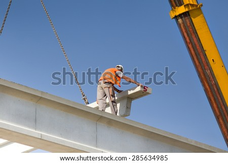Construction worker standing on concrete beam on height and placing truss lifted by crane - stock photo