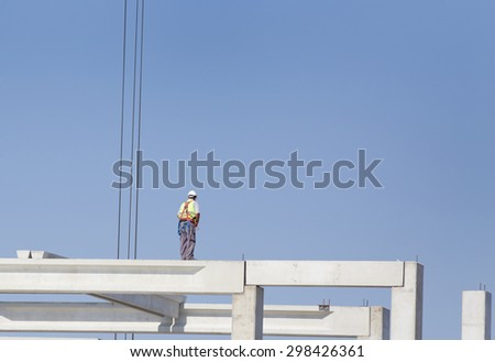 Construction worker standing on concrete beam on height and waiting crane to lift truss for installation - stock photo