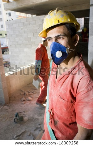 Construction worker stands in front of camera wearing blue dust mask. Vertically framed photo. - stock photo