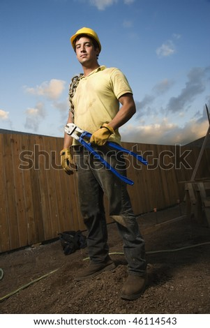 Construction worker stands on a mound of dirt while holding bolt cutters. He has a chain wrapped around his shoulder and a hardhat on. Vertical shot. - stock photo