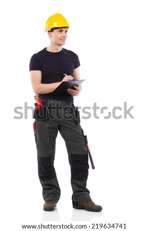 Construction worker taking a note. Construction worker in yellow helmet holding clipboard and writing.  Full length studio shot isolated on white. - stock photo