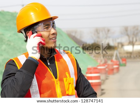 Construction worker talking on the phone - stock photo