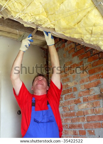 Construction worker thermally insulating house attic with rockwool - stock photo