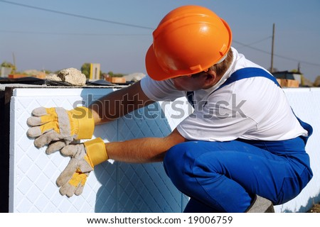 Construction worker thermally insulating house foundation walls with styrofoam boards - stock photo