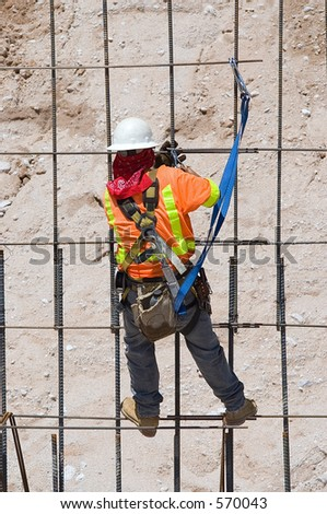 Construction worker tying rebar for concrete reinforcement on a road construction project - stock photo