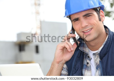 Construction worker using a mobile phone - stock photo