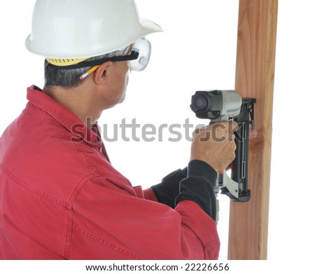 Construction Worker using a Nail Gun - isolated over white - stock photo