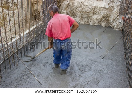 Construction worker using a shovel to flat concrete at construction site