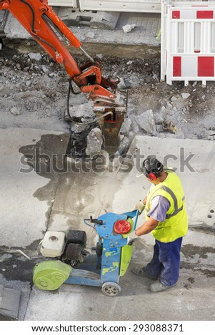 construction worker using cutting  pavement machine and large jackhammer in city street - stock photo