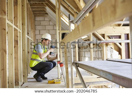 Construction Worker Using Drill On House Build - stock photo