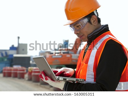 Construction worker using laptop with excavator on the background - stock photo