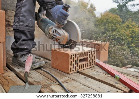 Construction worker using masonry saw to cut concrete blocks to build a new wall - stock photo