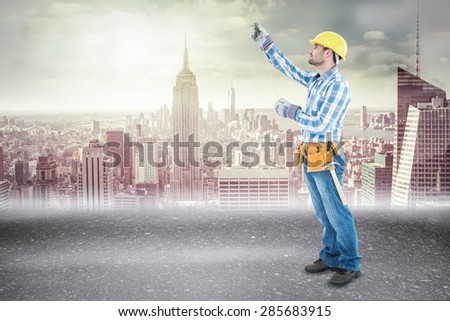 Construction worker using measure tape against road - stock photo