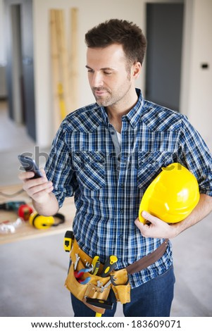 Construction worker using mobile phone during the working  - stock photo