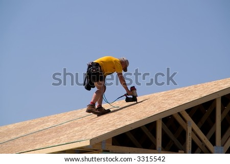 Construction worker using nail gun to nail osb sheeting on roof of a new home - stock photo