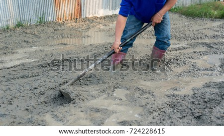 construction worker using the hoe to finish concrete floor