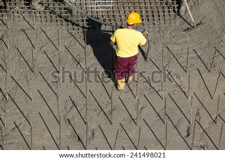 Construction worker vibrate concrete foundations - stock photo
