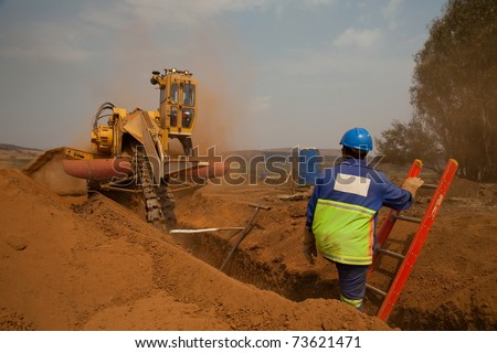 Construction worker watching a trencher machine digging and trench for a pipeline
