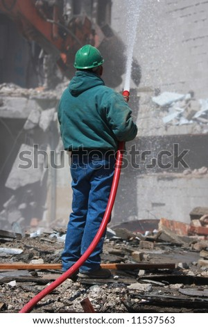 Construction Worker Watering Down Building Demolition
