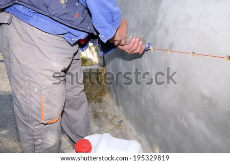 Construction worker waterproofing a wall.