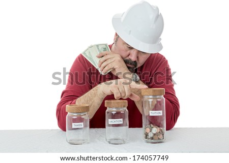Construction worker wearing a hardhat deciding over the use of money between, taxes, vacations or tuitions - stock photo