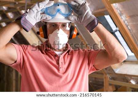 Construction worker wearing protective mask in attic - stock photo