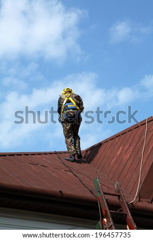 Construction worker wearing safety harness and safety line working on a roof - stock photo