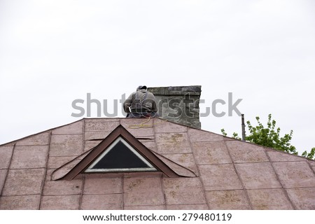 Construction worker wearing safety harness and  working on a roof. - stock photo