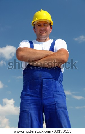 Construction worker wearing yellow helmet posing over blue sky with crossed hands