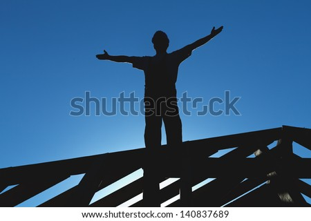 Construction worker welcoming the sun starting the workday - silhouette against the sky - stock photo