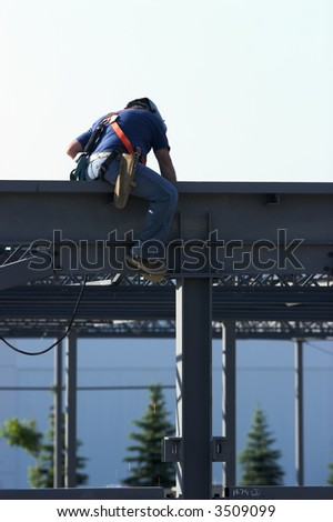 Construction worker welding on an I-beam on top of a building. - stock photo