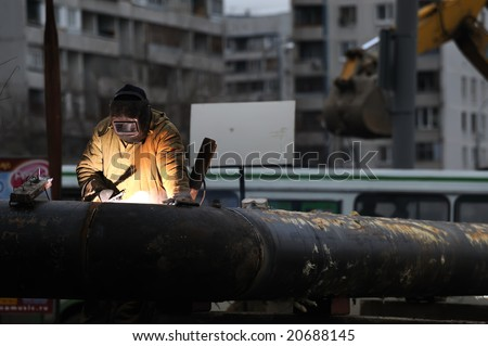 construction worker welding pipe - stock photo