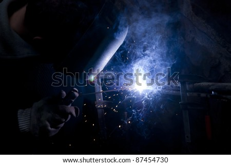 Construction worker welding steel. blue flame, sparks and smoke - stock photo