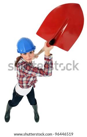Construction worker wielding a shovel - stock photo