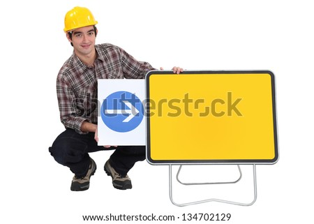 Construction worker with an arrow pointing to a blank sign - stock photo