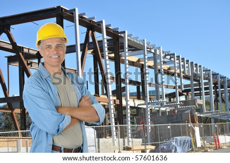 Construction worker with arms crossed on job site standing in front of new building frame. Horizontal format with man smiling at camera. - stock photo