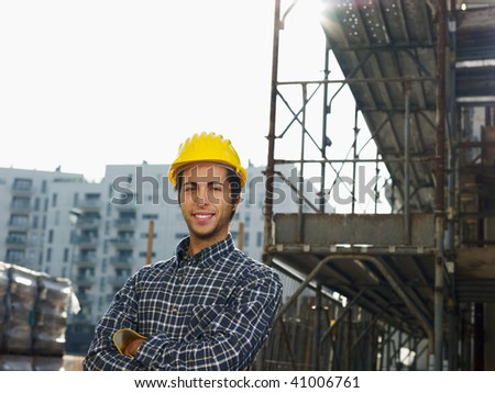 Construction worker with arms folded looking at camera. Copy space - stock photo