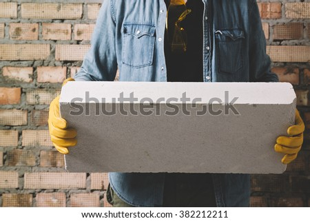 Construction worker with block - stock photo