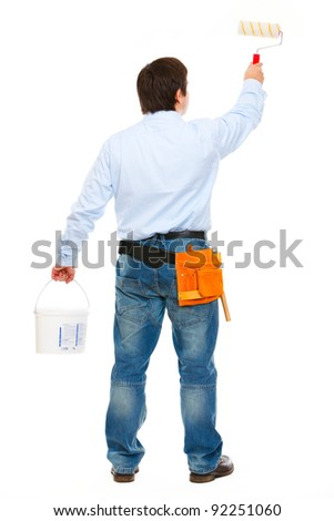 Construction worker with bucket and brush painting. Back view - stock photo