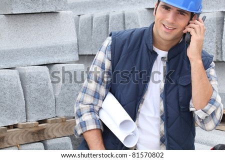 Construction worker with building plans and cellphone - stock photo