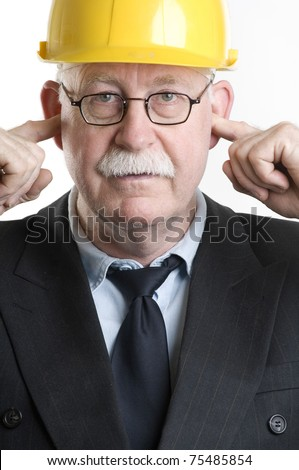Construction worker with fingers in his ears - stock photo