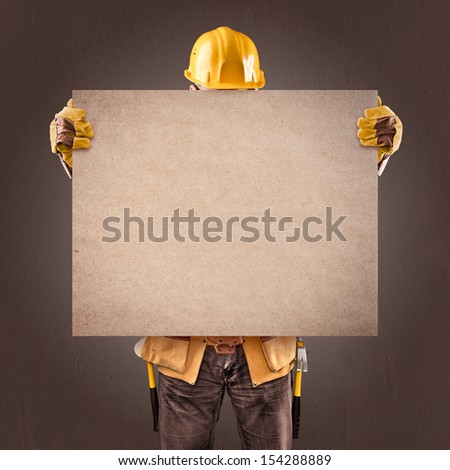 construction worker with information posters on a brown background - stock photo