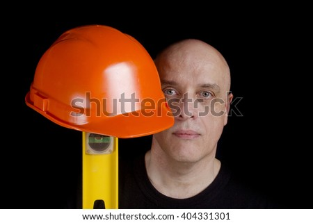 Construction worker with protection helmet and level on a black background - stock photo