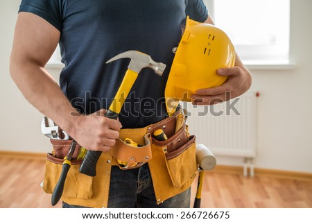 construction worker with tool belt, helmet and hammer - stock photo